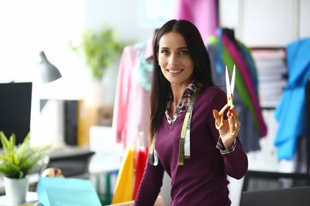 Portrait of trendy young girl posing in workplace in fashionable outfit. Joyful female looking at camera with gladness and calmness and holding special sewing utility. Fashioner workshop concept Reklamní fotografie