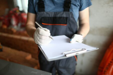 Focus on man hands holding pencil and write about process of unfinished room construction in order to make work easier and expertise all materials that people need. Building concept
