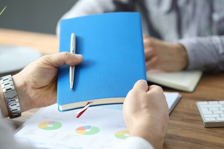 Male businessman hand hold blue diary with silver pen against office bacground. Business work concept 版權商用圖片