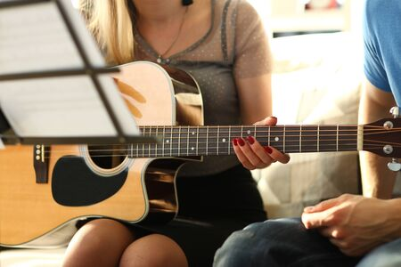 Talented Musician Pair Create Musical Tutorial. Man Teaching his Girlfriend Playing Acoustic Guitar, Composing Music while Sitting on Sofa at Living Room. Happy Couple in Relationship Hobby