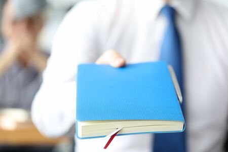 Male businessman hand hold blue diary against office bacground. Business work concept
