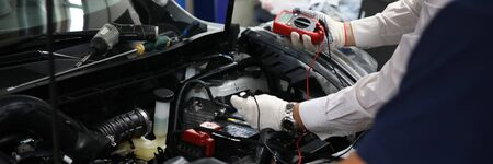 Two specialists of service for repairing wiring and computer diagnostics car solve problem engine malfunction. Serviceman collaborate education training concept. New technology studyng