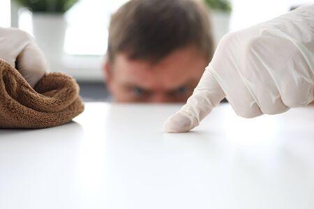 Concentrati sulla mano maschile guantata che tiene lo zerbino e fa scorrere la polvere sul posto di lavoro dell'ufficio bianco con concentrazione e diligenza dell'operatore intelligente dell'igiene. Piacevole concetto di pulizia. Sfondo sfocato Archivio Fotografico