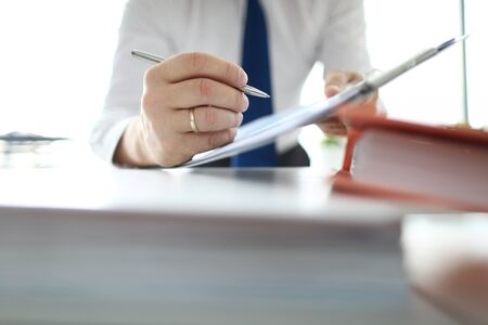 Focus on banking businessman hands pointing with metallic writing pen at business document in modern office. Businessman analyze marketing data. Audit concept Banco de Imagens