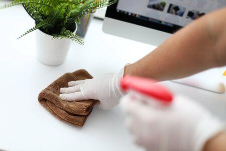 Concentrati sulla mano maschile guantata che tiene lo zerbino e spazza la polvere abitata da batteri nocivi dal posto di lavoro bianco con concentrazione e diligenza. Piacevole concetto di pulizia. Sfondo sfocato