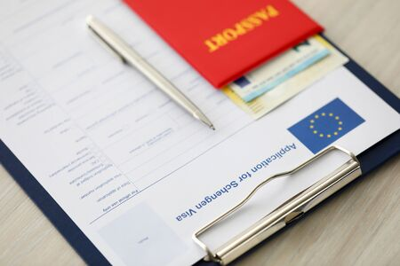 Focus on document case with application for schengen visa, passport, money and pen lying on table in office. Filling questionnaire form. Travelling abroad or immigration concept. Blurred background