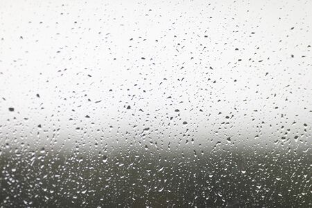 Close-up on window stained with autumn rain. Abstract texture with falling raindrops. Condensation on clear windowpane or transparent surface. Blurred background Reklamní fotografie