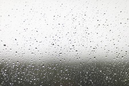 Nahaufnahme am Fenster mit Herbstregen befleckt. Abstrakte Textur mit fallenden Regentropfen. Kondensation auf klarer Fensterscheibe oder transparenter Oberfläche. Unscharfer Hintergrund