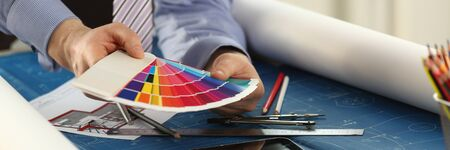 Architect Sample Selection Interior Design Concept. Creative Person Workplace. Closeup View of Hands of Male Designer Working with Color Palette at Office Desk. Building Blueprint Creation Stockfoto