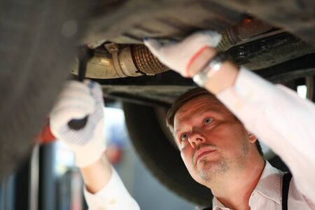 Portrait of hardworking man standing in garage and looking at underneath pipes of modern automobile in white gloves. Machinery repairman and service station concept Banco de Imagens