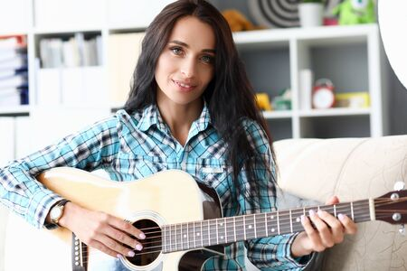Portrait of beautiful woman playing guitar in studio. Wonderful lady wearing fashionable checkered shirt and smart clock. Music concept. Blurred background