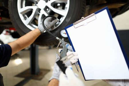 Focus on male arms holding special measuring utility and paper folder in white glove. Engineers working in garage with car lifts. Machinery repairman concept Stockfoto