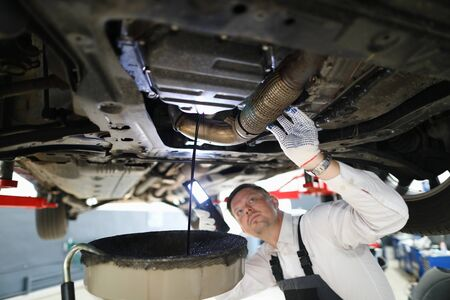 Focus on male examining modern high-tech automobile underneath pipes with pouring oil in white gloves with precise accuracy. Machinery repairman concept