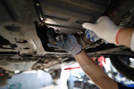 Konzentrieren Sie sich auf fleißige männliche Hände, die moderne High-Tech-Automobile unter Rohren in weißen Handschuhen mit präziser Genauigkeit untersuchen. Maschinenmechanikerkonzept Standard-Bild