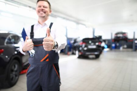 Focus on hand of happy engineer man showing thumb up and standing in modern car maintenance garage with automobiles. Machinery repairman concept. Blurred background