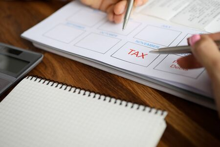 Two business people hand holds siver pen against tax sign form background. Preparation of the annual financial report return concept