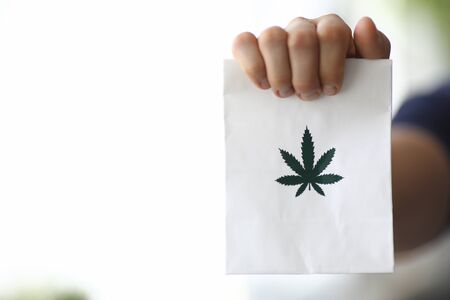 Focus on male hand holding white small paper bag with green cannabis symbol on it. Healthcare and medicines concept. Copy space in left side. Blurred background