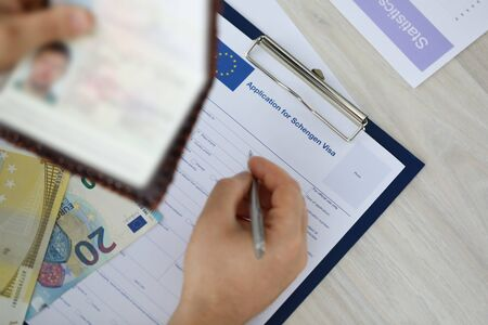 Focus on male holding identity documents and filling application for schengen visa Businessman sitting at wooden table. Travelling abroad or immigration concept. Blurred background
