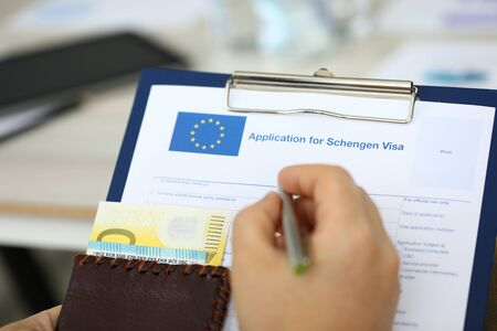 Focus on male hand holding paper folder, passport with money and answering to questions posed in application for schengen visa. Travelling abroad and immigration concept. Blurred background