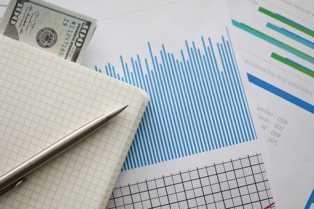Close-up of important documents with graphs, charts and currency banknotes. Notepad and pen lying on paper. Stock Exchange, Securities Market and business concept