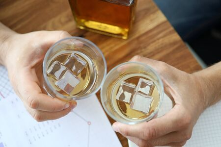Top view on employee hands holding two glass of whiskey. Alcohol beverage with ice cubes. Workers sitting at table with papers and drink, relaxation in office