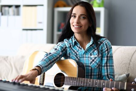 Portrait of wonderful female learning new musical composition. Beautiful woman accompanying on piano and guitar. Music and art concept. Blurred background Stockfoto