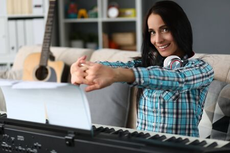 Portrait of smiling girl resting after playing on synthesizer. Tired female doing hand gymnastics. Cheerful pianist looking at camera with gladness. Music concept. Blurred background Stock fotó