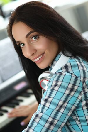 Close-up of wonderful lady creating new musical composition. Beautiful woman with brunette hair looking at camera with happiness. Music concept. Blurred background