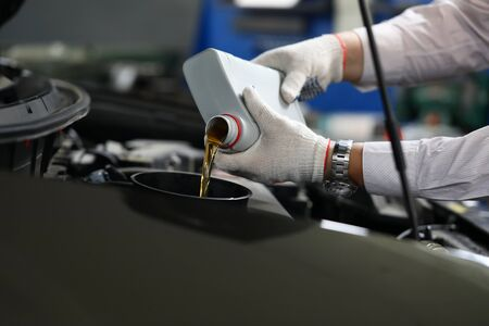 Focus on automechanic male hands in white gloves using canister of machinery liquid and precisely pouring under hood of sportcar. Automotive checkup concept