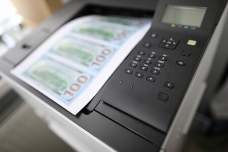 Sheet of paper printed on a printer with fake dollars banknote background