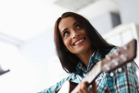 Close-up of beautiful woman learning new musical composition. Wonderful female wearing checkered fashionable blouse. Art music concept. Blurred background