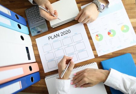 Businessman and businesswoman make work plan 2020 on office table with folder paper background. Business paperwork concept Stock Photo