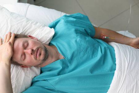 Concepto de daño por automedicación. El hombre no fue a los médicos durante mucho tiempo y terminó en cuidados intensivos. El paciente se acuesta en la cama y sufre
