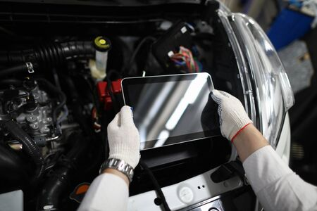 Close-up of special digital tablet used for automobile checkup and fixing damaged car parts. Mechanic in white gloves and working outfit in service station. Copy space on screen. Automotive check