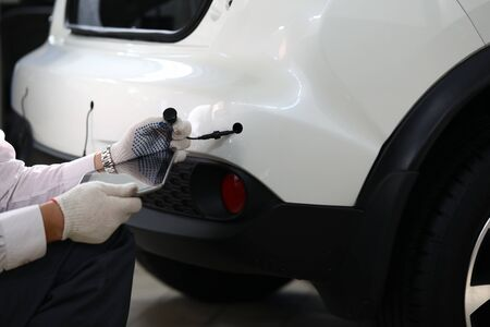 Close-up of male automechanic hands holding modern digital tablet and car tube in white gloves and working. Smart mechanic at service station. Automotive check concept. Copy space on screen