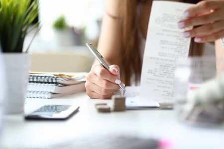 Focus on smart businesswoman sitting indoors and counting presumable profits from charts in important paper tablet with numbers. Lady making notes. Office concept. Blurred background