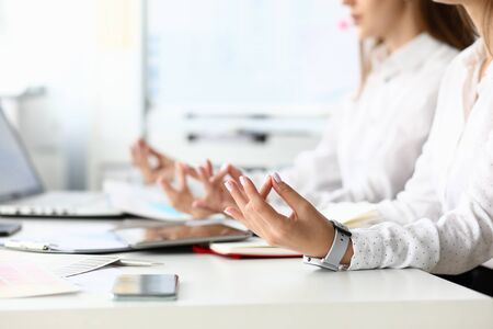 Focus on tender female hands of hardworking businesswoman positioning arms in special relaxing pose at modern workplace with friendly colleagues. Business teamwork concept