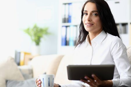 Portrait of pretty businesswoman sitting in modern office and drinking hot delicious beverage. Beautiful woman holding high-tech tablet. Hardworking lady concept