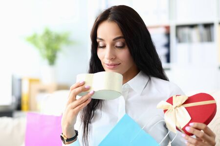 Portrait of joyful brunette sitting in modern office and looking at multicolored packet. Pretty businesslady holding heartshaped box. Shopping concept. Blurred background
