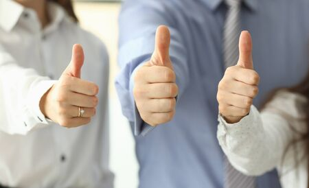 Focus on tender female and male hands showing big thumb up and posing at modern workplace. Business People working in office together. Teamwork concept