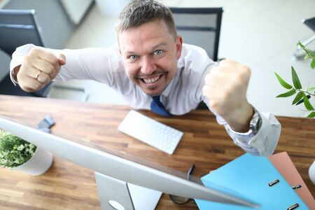 Top view of cheerful businessman standing near computer and looking at camera with happiness. Worker winning prize or signing profitable contract. Blurred background Banco de Imagens