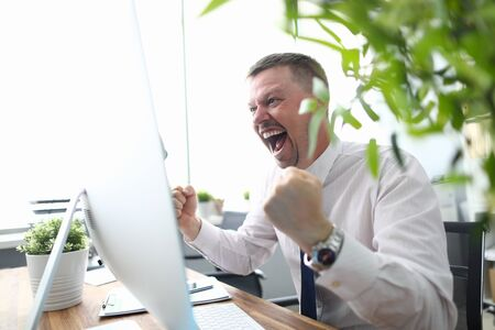 Portrait of cheerful man looking at computer monitor with gladness and making successful gesture. Businessman finishing project and wins big. Blurred background 写真素材