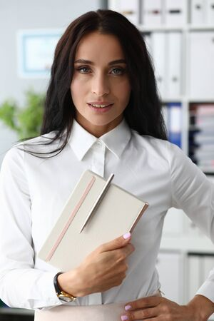 Portrait of smiling businesswoman standing indoors and looking at camera with concentration and self-respect. Smiling woman holding paper tablet with pen. Strict lady worker concept