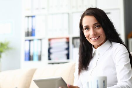 Portrait of joyful businesswoman sitting on comfortable sofa and looking at camera with calmness and self-confidence. Beautiful woman holding high-tech gadget. Hardworking lady worker concept