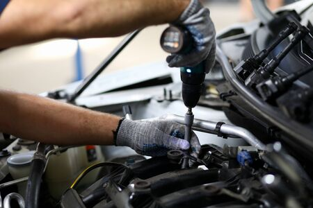Close-up on automechanic hands checking automobile parts. Machine details necessarily used for perfect auto functionality in modern engineering service station. Automotive checkup concept