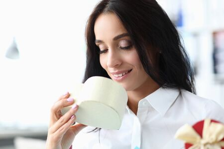 Portrait of smart businesswoman sitting in modern office and looking at white heartshaped box with happiness and joy. Shopping and gift concept. Blurred background Stock fotó