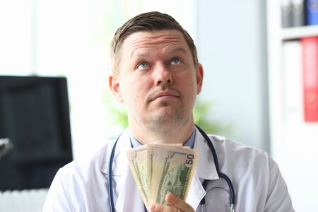 Portrait of smart professional physician in modern hospital office holding fan of green banknotes and looking up with satisfaction. Healthcare and clinic concept