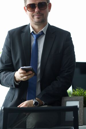 Millennial businessman hold smartphone. Handsome man in stylish suit. Business sucsess concept. Banco de Imagens