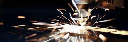 Lasergesneden machinekop voor metaalverwerking metallurgische fabrieksvonkachtergrond. Productie van afgewerkte onderdelen voor autoproductieconcept