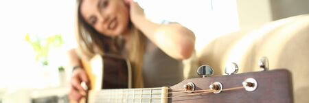 Female Bass Guitarist Performing Music at Home. Beautiful Musician Sitting on Comfortable Sofa Holding Strings Musical Instrument. Focus on Neck and Guitar Headstock. Natural Light in Room